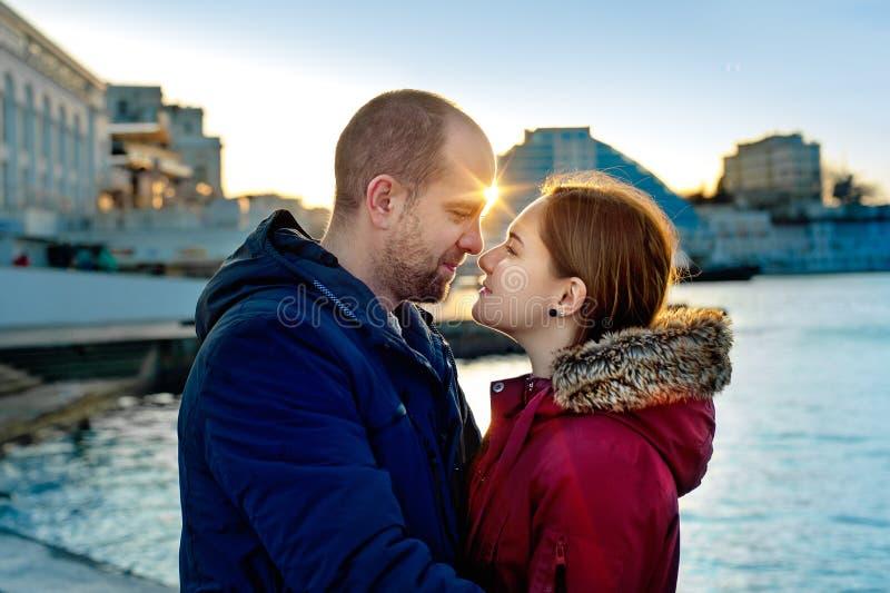 Lyckliga älska par som kramar i stad Stående av den unga attraktiva le mannen och kvinnan som kopplar av på pir vid havet arkivbilder