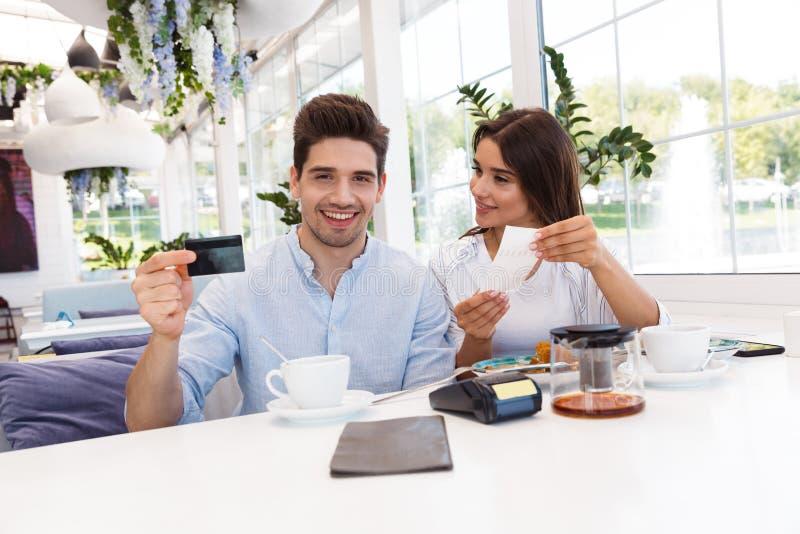 Lyckliga älska par som sitter i kaféinnehavkreditkort och kontroll royaltyfri foto