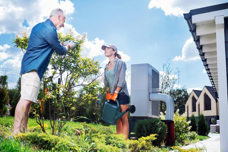 Lyckliga älska par som tillsammans bevattnar deras lilla träd i trädgården royaltyfri bild