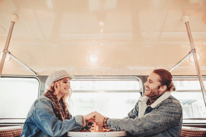 Lyckliga ?lskade par som rymmer h?nder i busskaf? royaltyfria foton