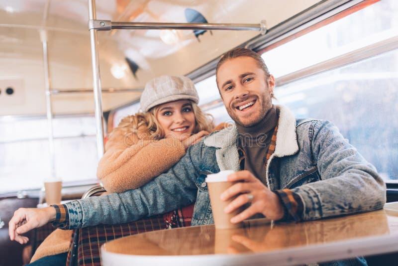 Lyckliga ?lskade par som sitter i kaf?buss arkivbild