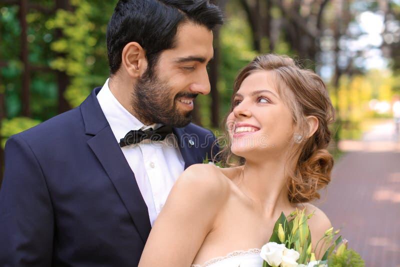 Lyckliga älskvärda nygifta personer utomhus arkivbilder