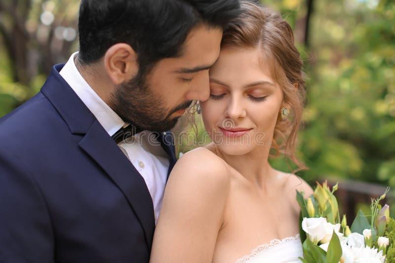 Lyckliga älskvärda nygifta personer utomhus royaltyfria bilder