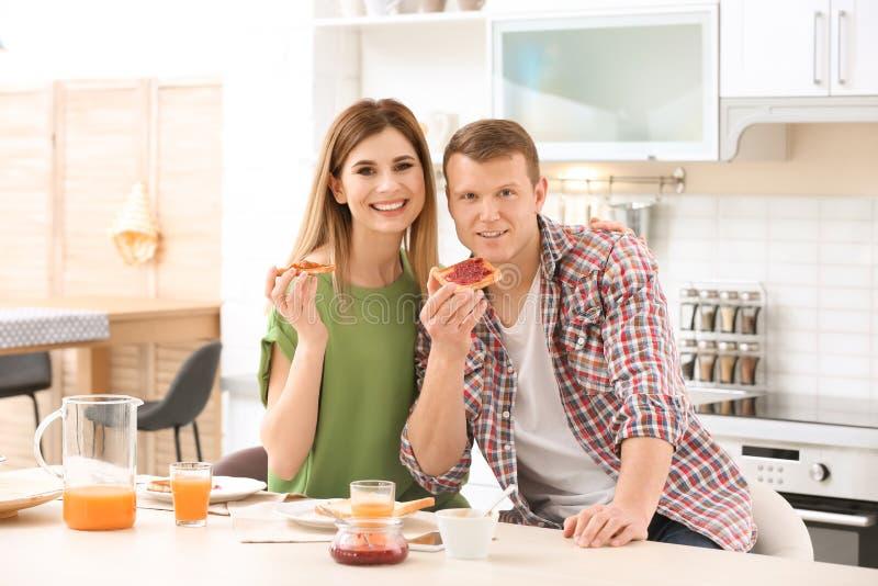 Lyckliga älskvärda par som har frukosten med smakligt bröd på tabellen i kök royaltyfri fotografi
