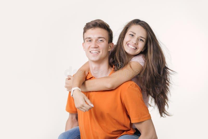 Lyckliga älskvärda par som kramar och ler se kameran på vit bakgrund arkivfoton