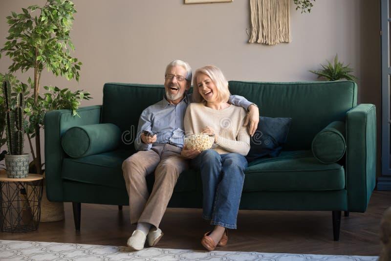 Lyckliga åldriga par, hållande ögonen på tv för fru och för make och ätapopcorn arkivfoto