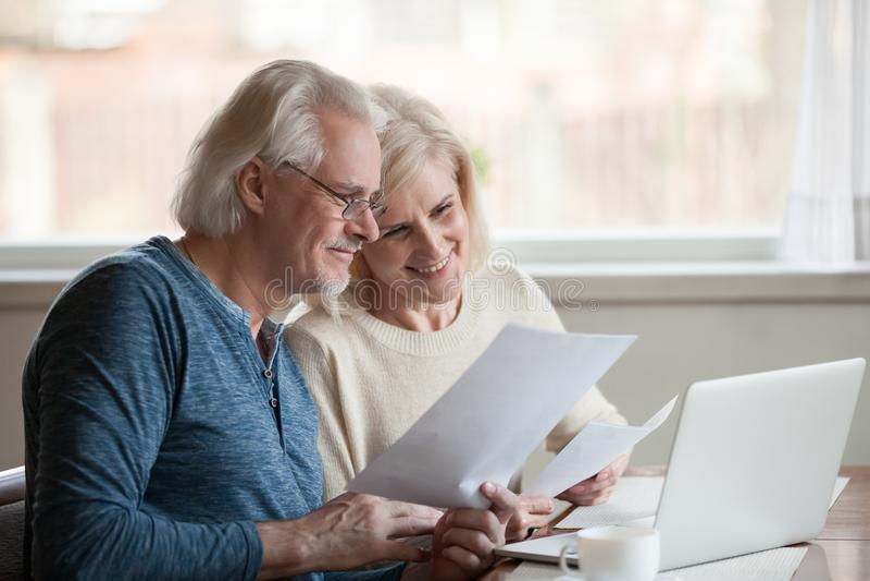 Lyckliga åldriga par som tillfredsställs med lätta online-bankrörelsen genom att använda lapto royaltyfria foton