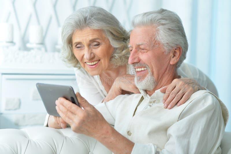 Lyckliga åldringpar genom att använda en minnestavladator royaltyfri foto