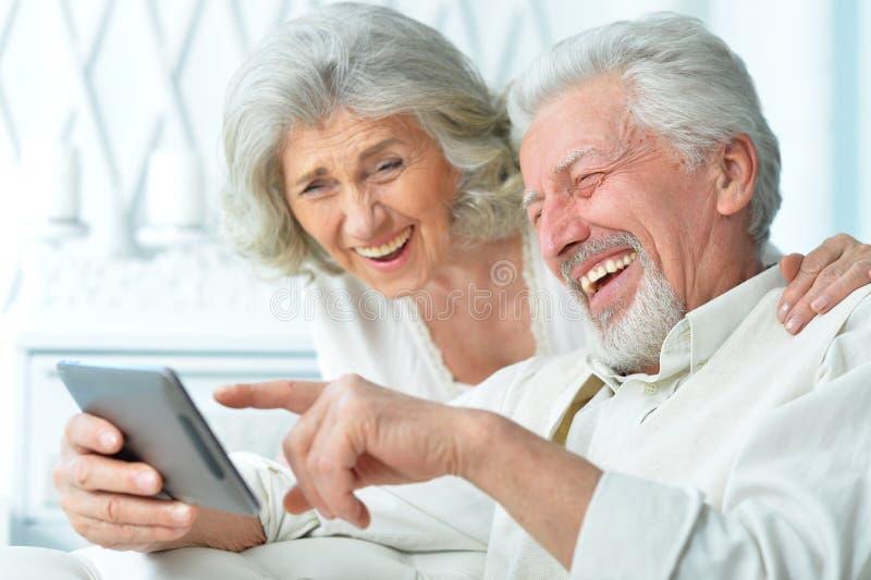 Lyckliga åldringpar genom att använda en minnestavladator arkivbild