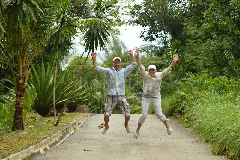 Lyckliga åldringpar i tropisk skog royaltyfria bilder