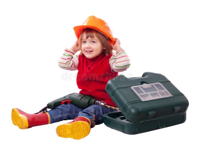 Det lyckliga barnet i hardhat med bearbetar royaltyfria foton