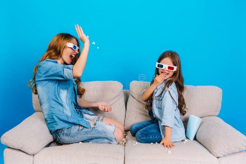 Lyckliga ögonblick av den nätta unga modern som har gyckel med dottern på soffan på blå bakgrund Trendig framtidsutsikt royaltyfria foton