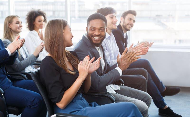 Lyckliga affärskollegor som applåderar händer på konferensen royaltyfri fotografi
