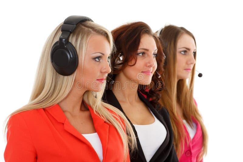 Lyckliga affärskvinnor med hörlurar med mikrofon. royaltyfri fotografi