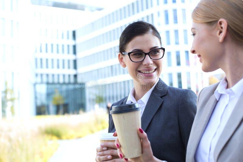 Lyckliga affärskvinnor som samtalar medan hållande disponibla koppar utomhus arkivbilder