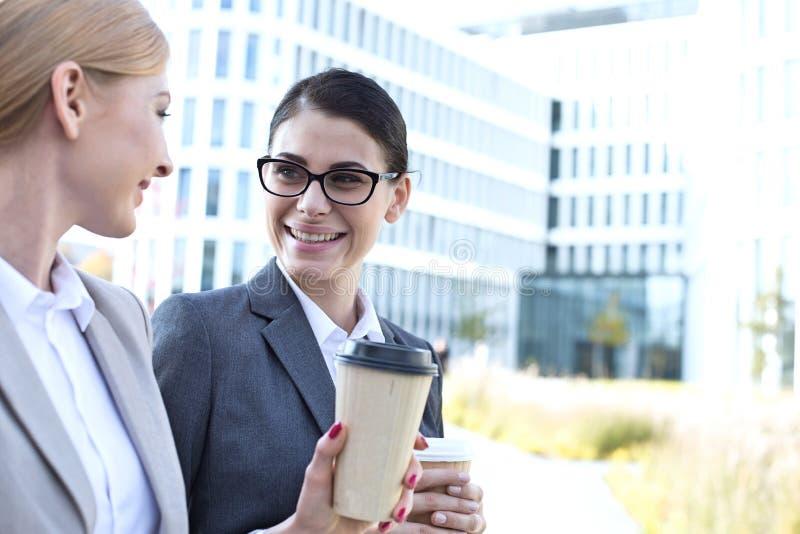 Lyckliga affärskvinnor som samtalar medan hållande disponibla koppar utomhus arkivfoto