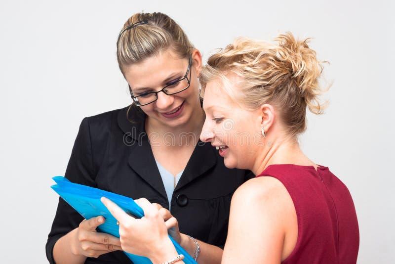 Lyckliga affärskvinnor som ser dokumentet royaltyfria foton
