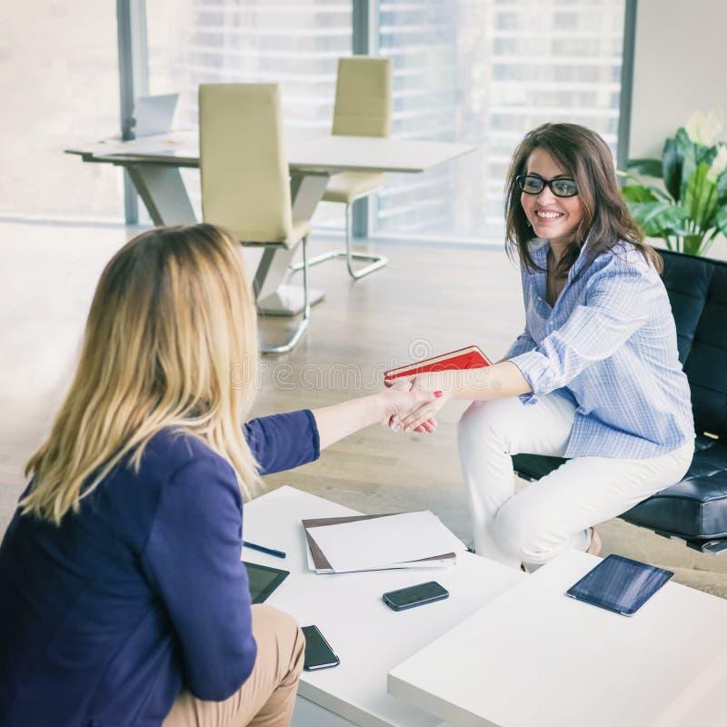 Lyckliga affärskvinnor som skakar händer arkivbilder