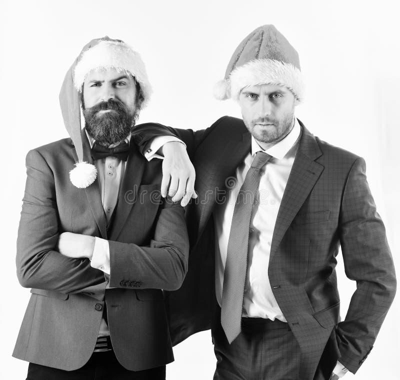 Lyckliga affärsmän i jultomtenhattar som lutar på de fotografering för bildbyråer