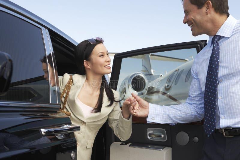Lyckliga affärspar som av får en bil fotografering för bildbyråer