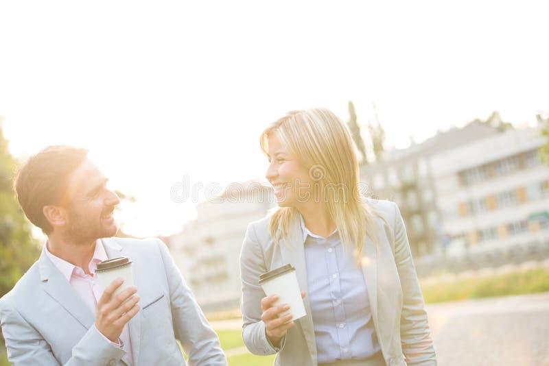 Lyckliga affärspar som samtalar medan hållande disponibla koppar i stad arkivfoto