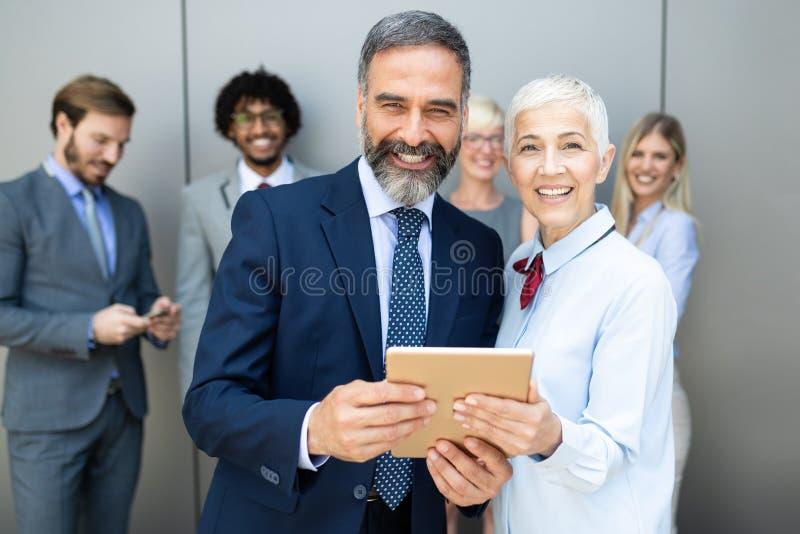 Lyckliga aff?rskollegor i modernt kontor genom att anv?nda minnestavlan arkivfoto