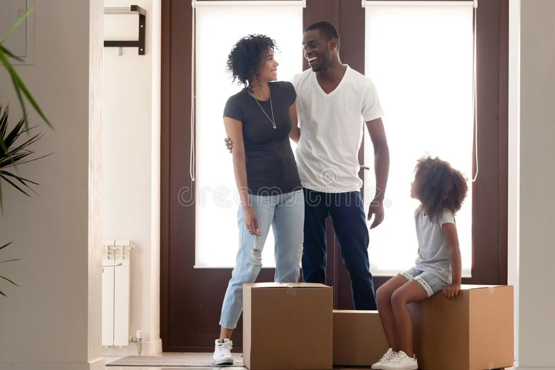 Lyckliga afrikansk amerikanföräldrar som står i nytt hus med dottern arkivfoton