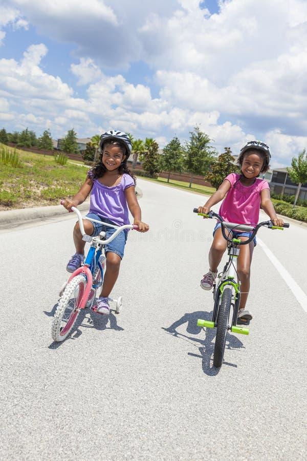 Lyckliga afrikansk amerikanflickor som rider cyklar royaltyfri bild