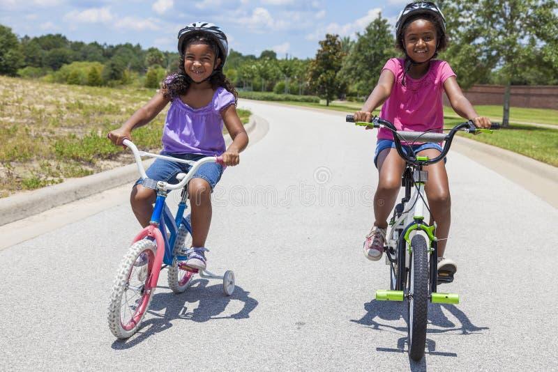 Lyckliga afrikansk amerikanflickor som rider cyklar arkivfoto