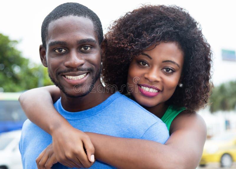 Lyckliga afrikansk amerikanpar som är utomhus- i staden royaltyfria foton