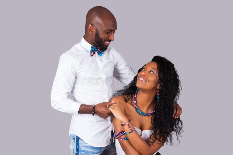 Lyckliga afrikansk amerikanpar som bär traditionell kläder över G fotografering för bildbyråer