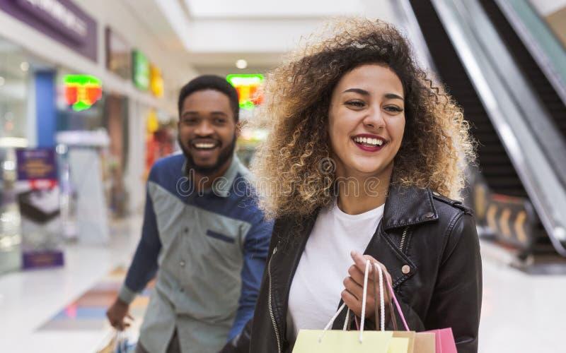 Lyckliga afrikansk amerikanpar som bedrar i köpcentrum royaltyfri fotografi