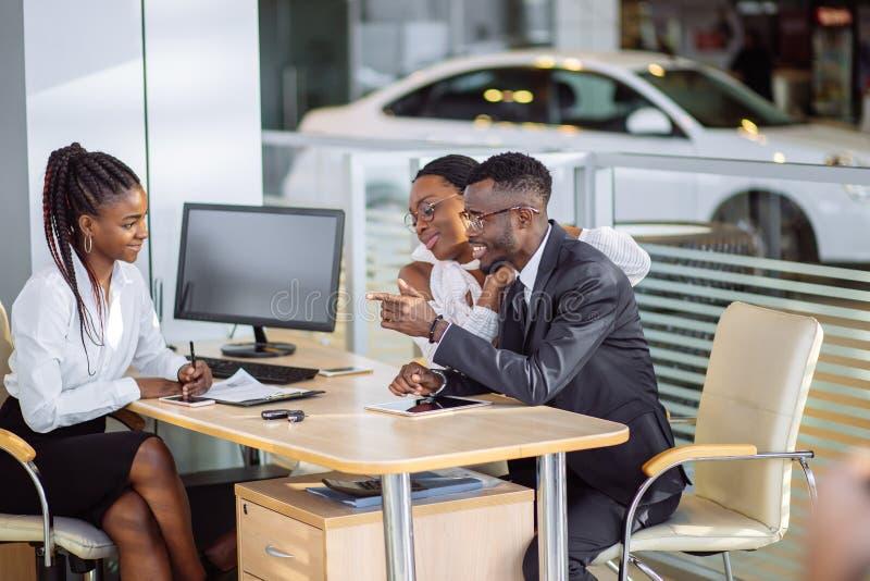 Lyckliga afrikanska par med återförsäljareköpandebilen i auto show eller salong royaltyfri fotografi