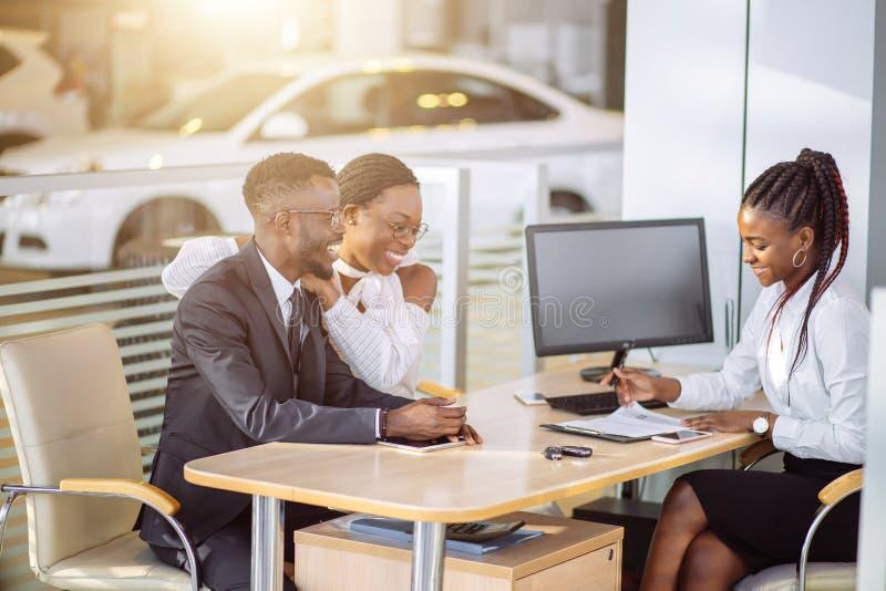 Lyckliga afrikanska par med återförsäljareköpandebilen i auto show eller salong arkivfoto