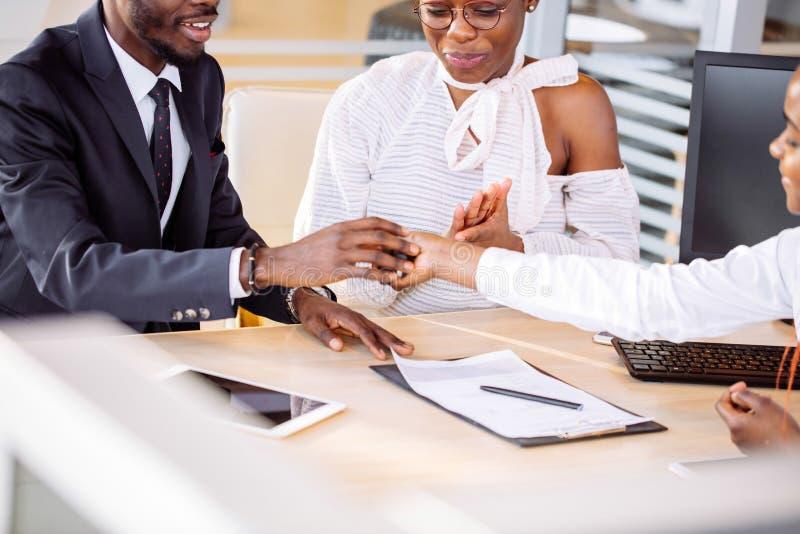 Lyckliga afrikanska par med återförsäljareköpandebilen i auto show eller salong fotografering för bildbyråer