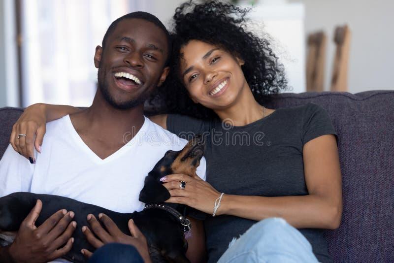 Lyckliga afrikanska par som spelar med hunden som sitter på soffan, stående arkivbilder