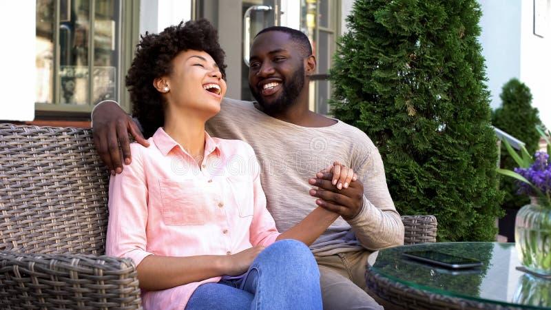 Lyckliga afro--amerikan par som tycker om det romantiska datumet, sittande kafé, förbindelse arkivfoto