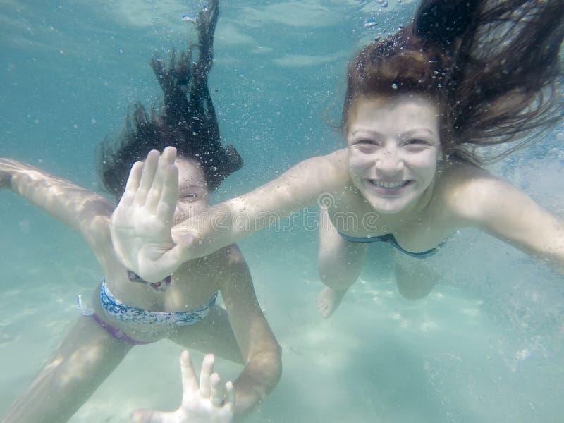 Lyckliga aktiva undervattens- flickor som simmar i havet och har gyckel på familjsommarsemester arkivbild