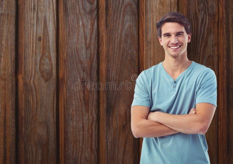 Lyckliga anseendearmar för ung man korsade mot träväggen arkivfoton