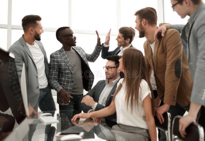 Lyckliga anställda som gratulerar sig på framgång arkivbild