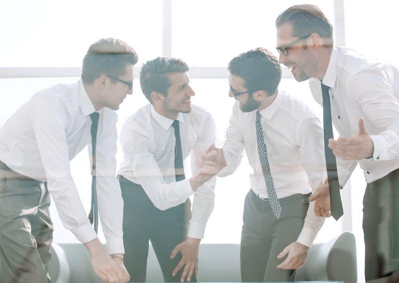 Lyckliga anställda som står nära kontorsskrivbordet arkivfoton