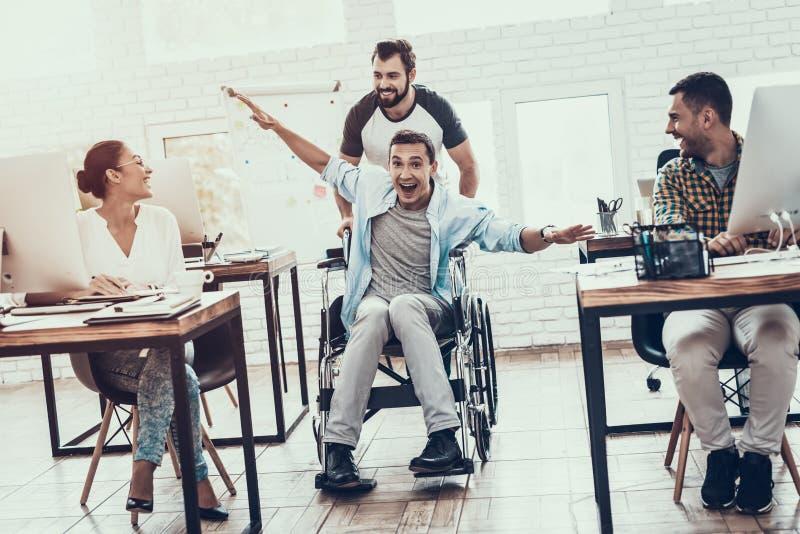 Lyckliga arbetare har gyckel på avbrott i modernt kontor arkivbilder