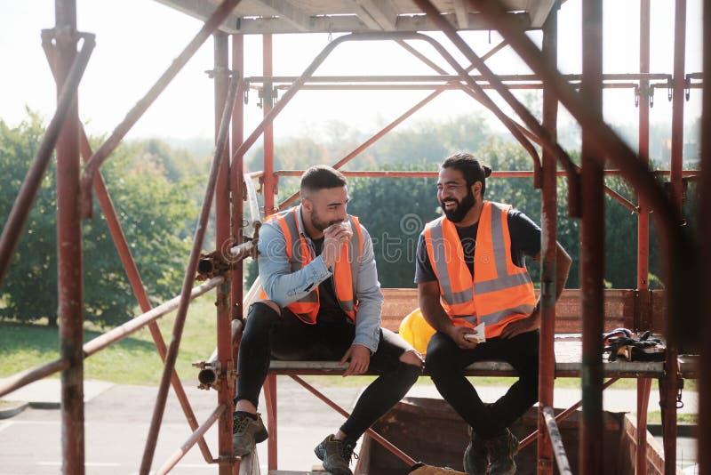Lyckliga arbetare i konstruktionsplats under lunchavbrott arkivbilder