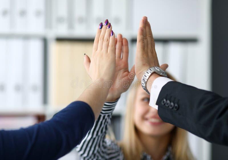Lyckliga arbetare i regeringsställning som firar ny företags prestation royaltyfri bild