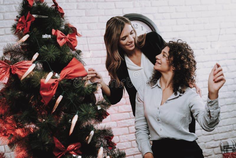 Lyckliga arbetare som i regeringsställning dekorerar julgranen arkivbilder