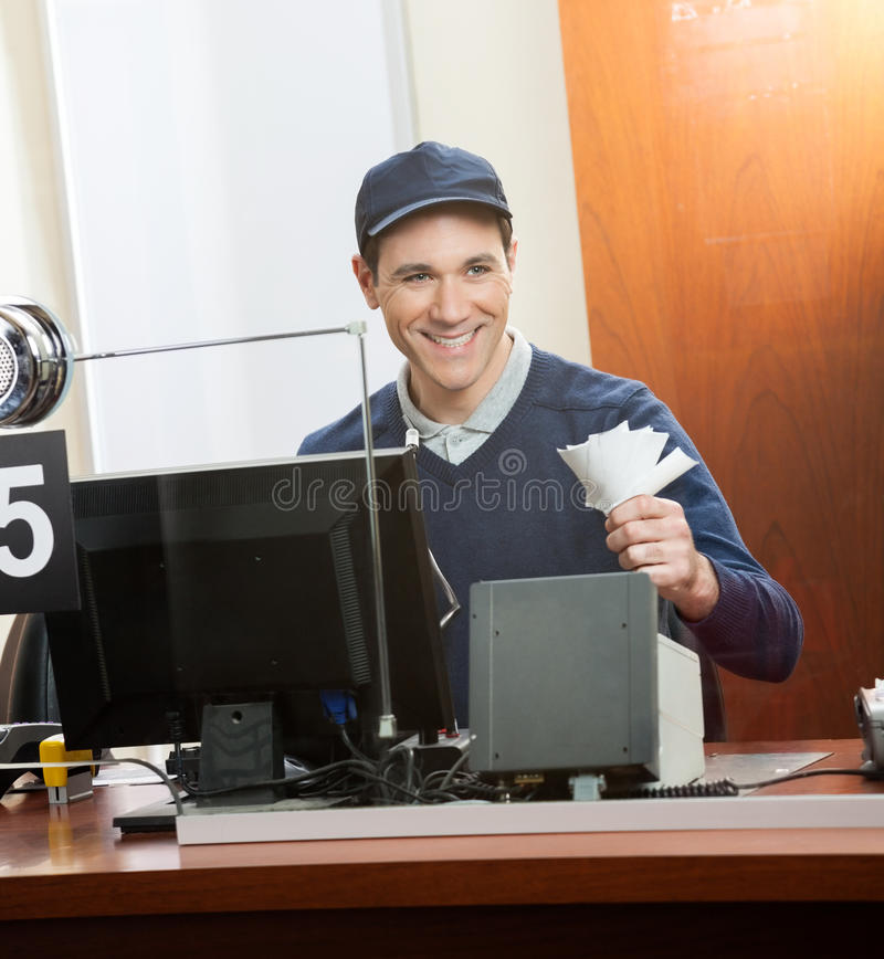 Lyckliga arbetarinnehavbiljetter på biljettkontoret royaltyfri bild