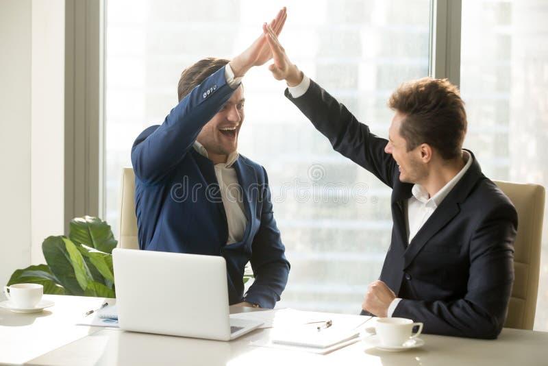 Lyckliga arbetsgivare som firar prestationer i arbete royaltyfri bild