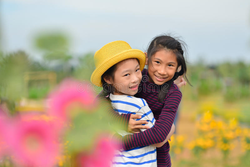 Lyckliga asiatiska barn i blommafält fotografering för bildbyråer