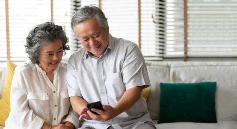 Lyckliga asiatiska höga par genom att använda smartphoneteknologi, medan le och sitta på soffan på deras hem arkivfoton