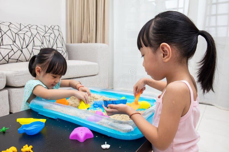 Lyckliga asiatiska kinesiska små flickor som hemma spelar kinetisk sand fotografering för bildbyråer